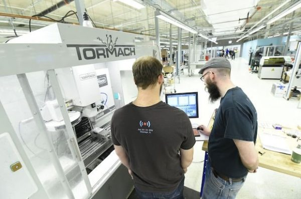 two males talking in front of 3D printer