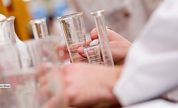 view of hands among chemistry glassware
